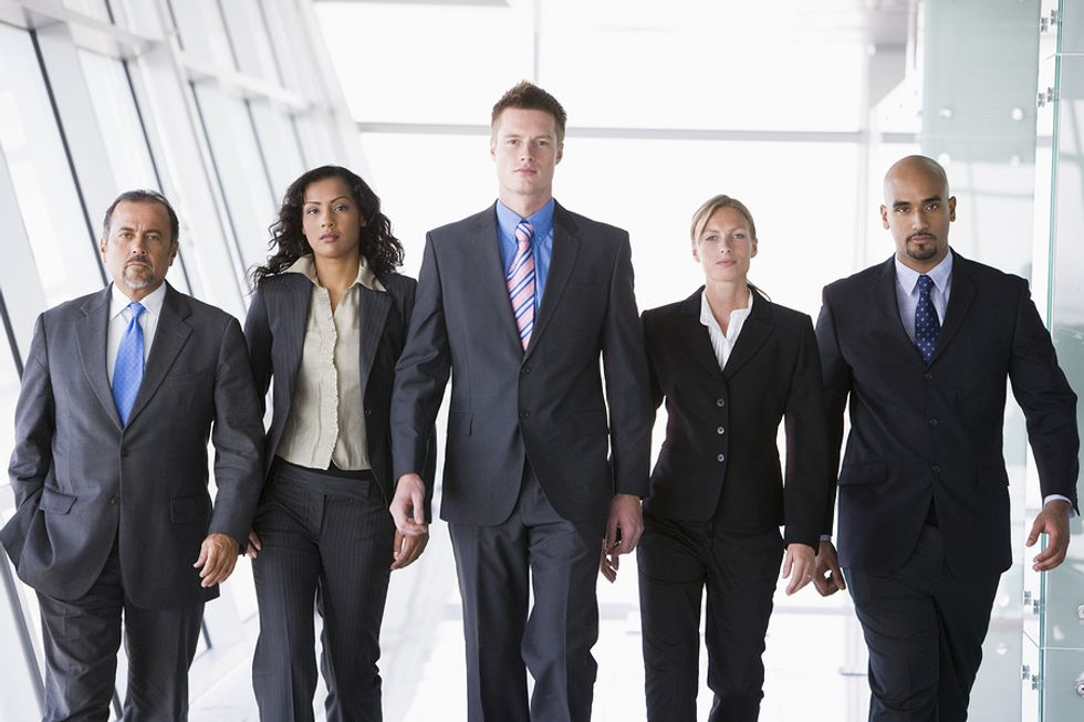 A group of co-workers walk together at work.