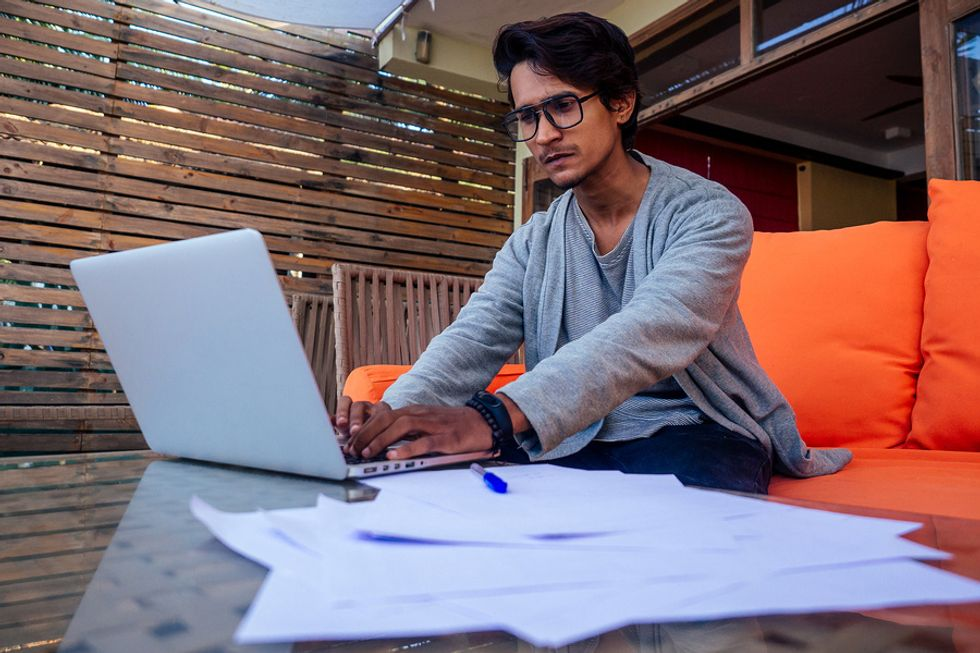 Young man sitting on a couch and working on his laptop as he freelances overseas.