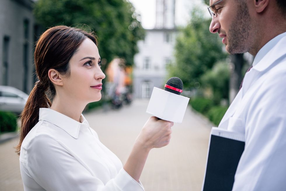 Young female journalist interviewing a doctor as she does an overseas assignment.