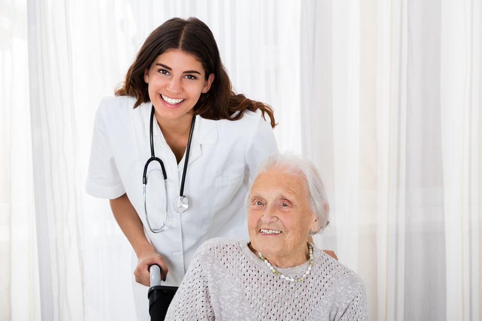 Young female traveling nurse helping an older woman in a wheelchair.