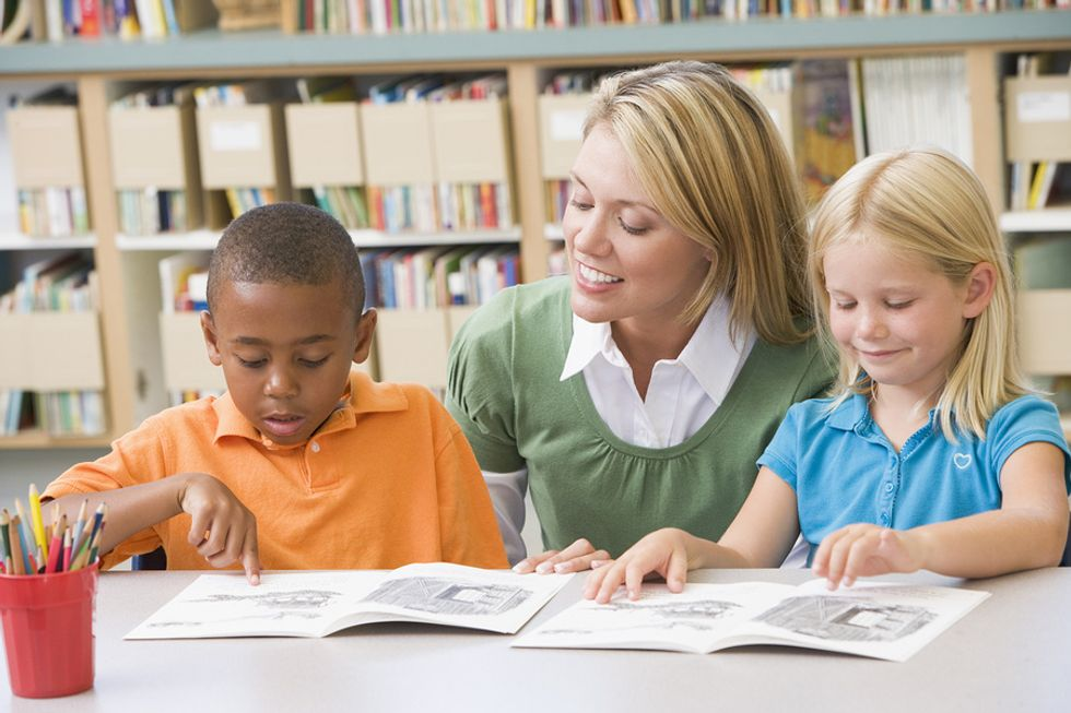 A teacher helps her students read after getting the job