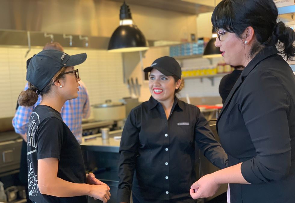 Chipotle employees chat during their shift.