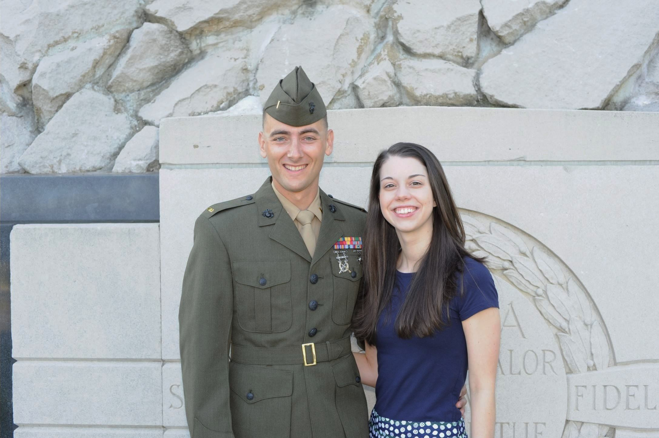 A Marine second lieutenant stands with a woman in front of a war memorial.