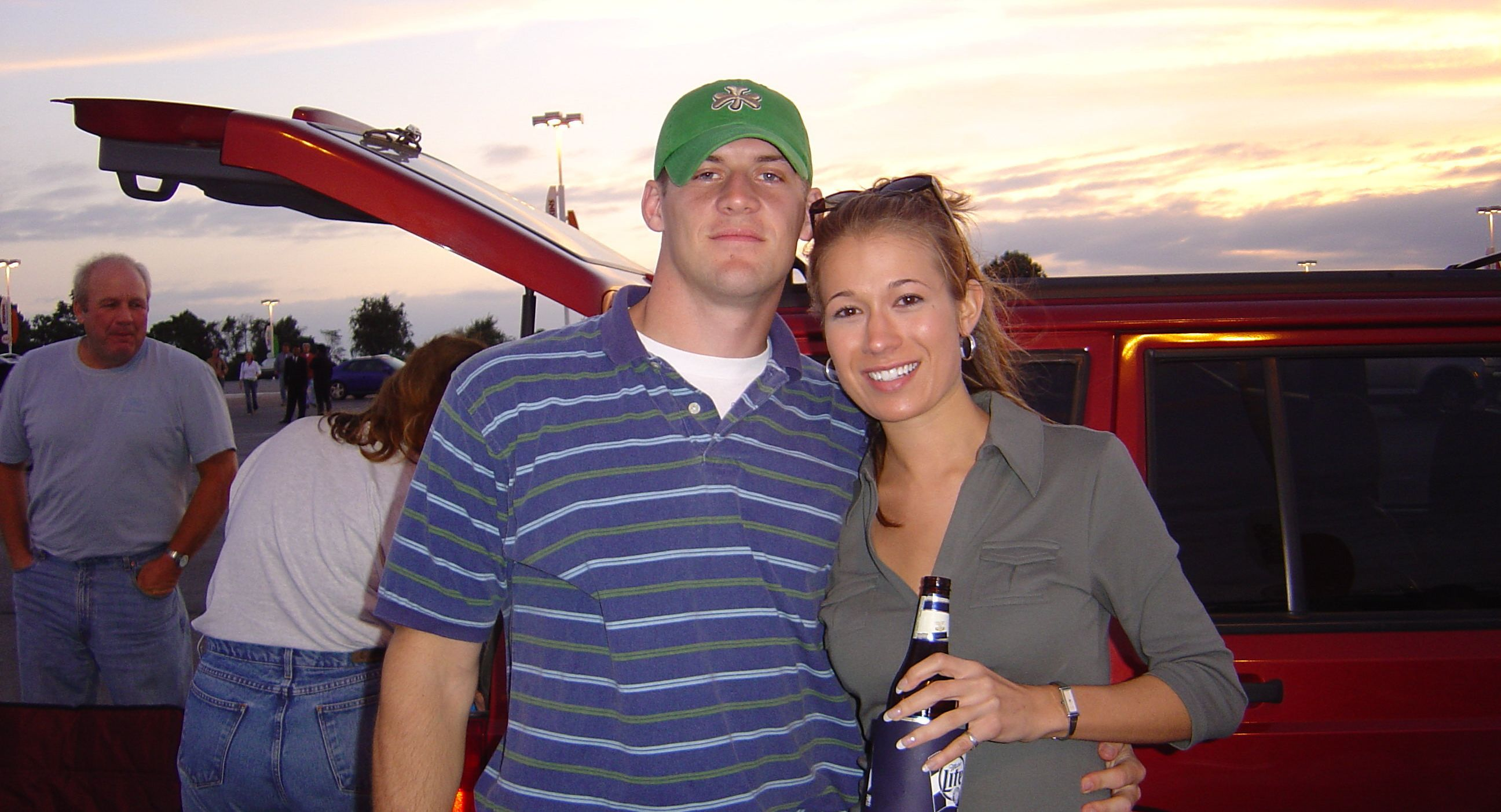 A woman holding a beer stands with a man in a parking lot in front of a vehicle with its tailgate open.