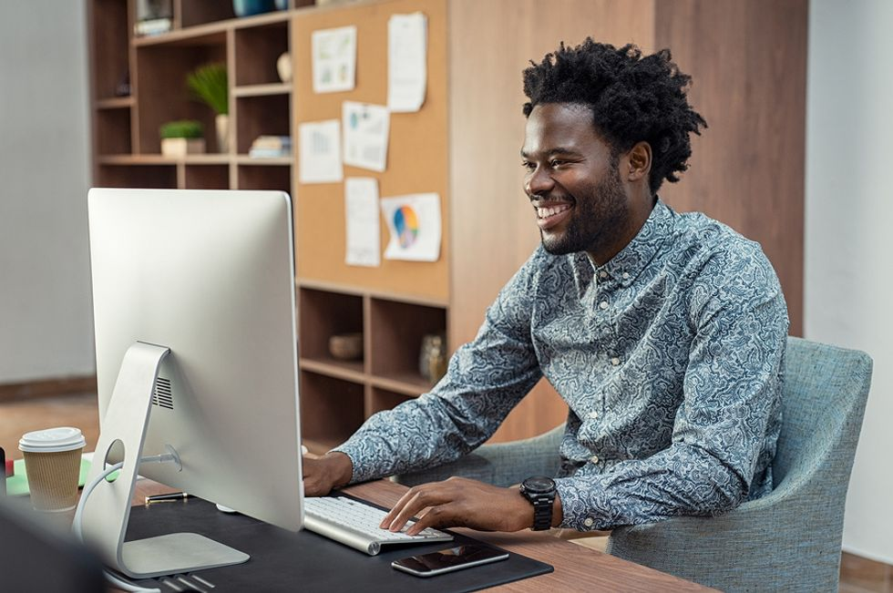 Young professional man smiling at his desk in an office, feeling happier about his work situation.