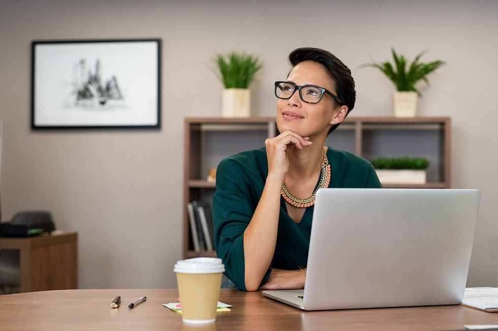 Young woman thinking positively about her work while working at her desk.
