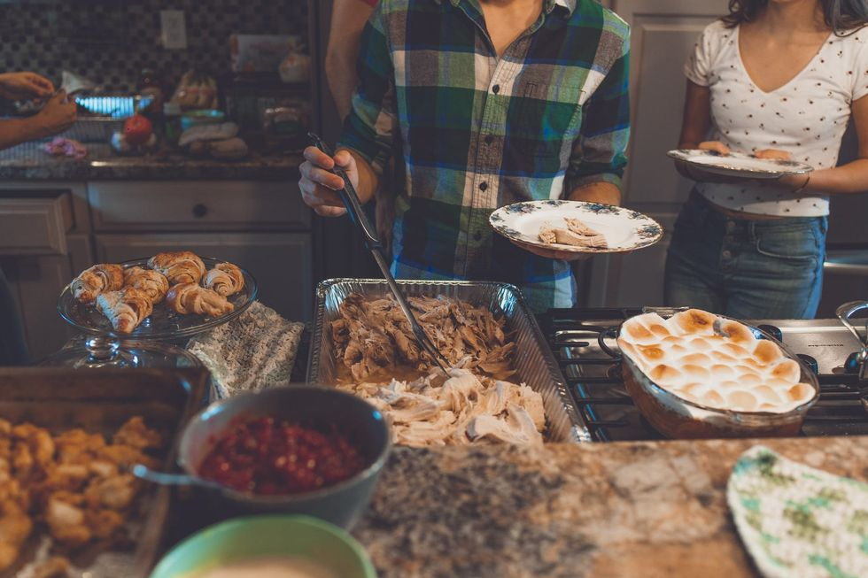 Buffet-style spread with person in plaid shirt taking food
