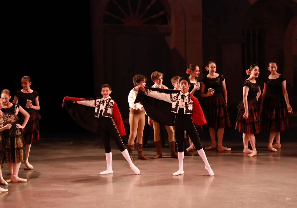 Students in performance. Two boys in torero costumes are center stage, holding one side of the red cap out to the side with the opposite leg in tendu. Crowds of other dancers in Spanish themed costumes are behind them.