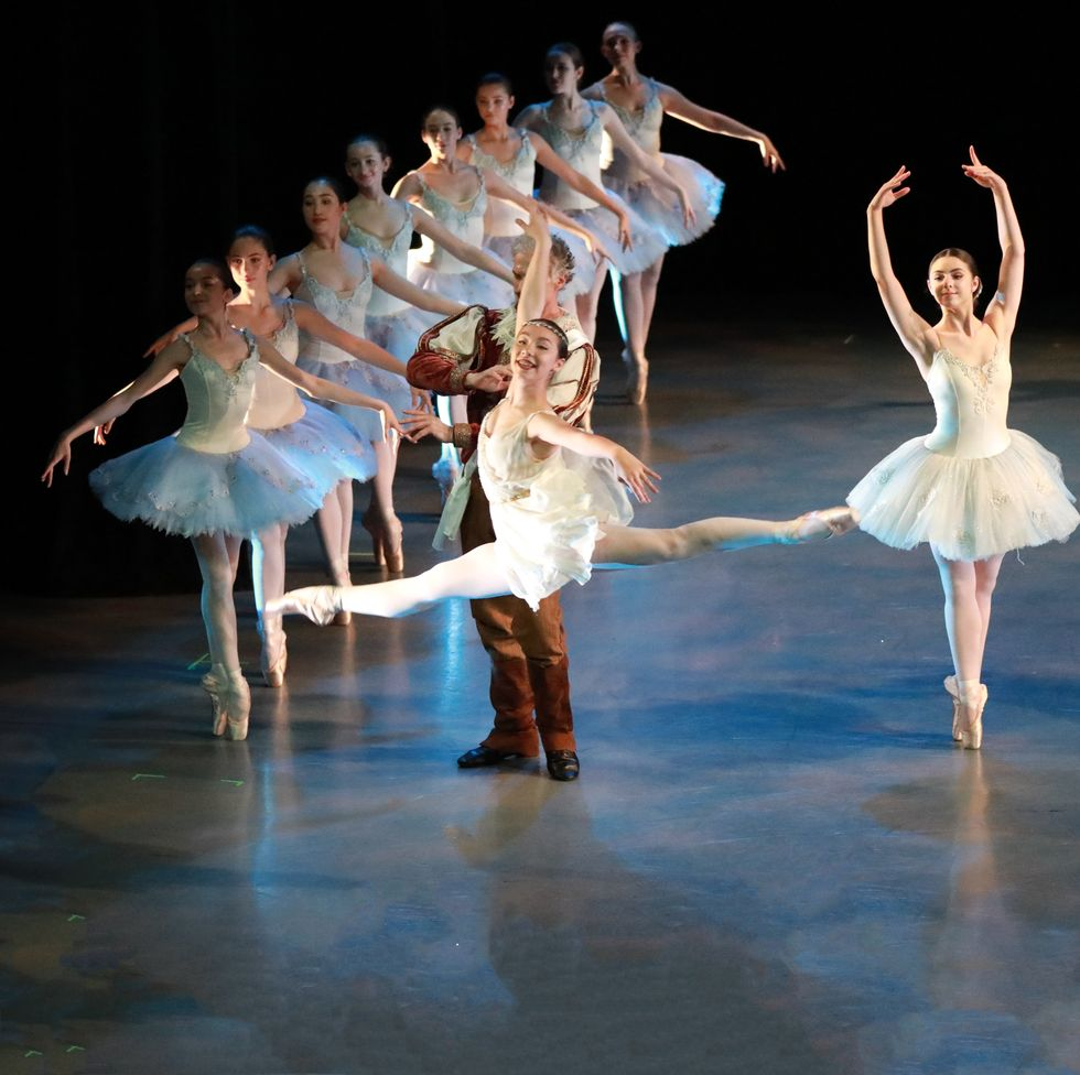 Students in performance. Rows of girls in white and blue romantic tutus, en pointe in fifth position with their arms to the sides. A girl center stage is mid-leap, in a flowy dress.