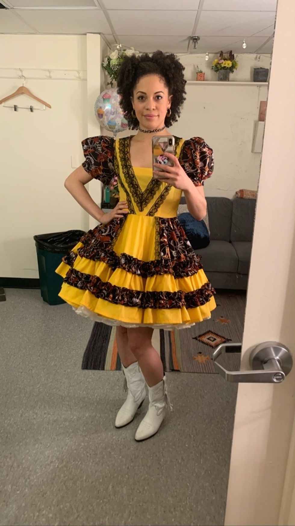 Hutchings taking a mirror selfie in her dressing room. She is wearing a poofy yellow dress with black lace detail, with a choker on her neck and hoop earrings. Her afro is pulled back part of the way.