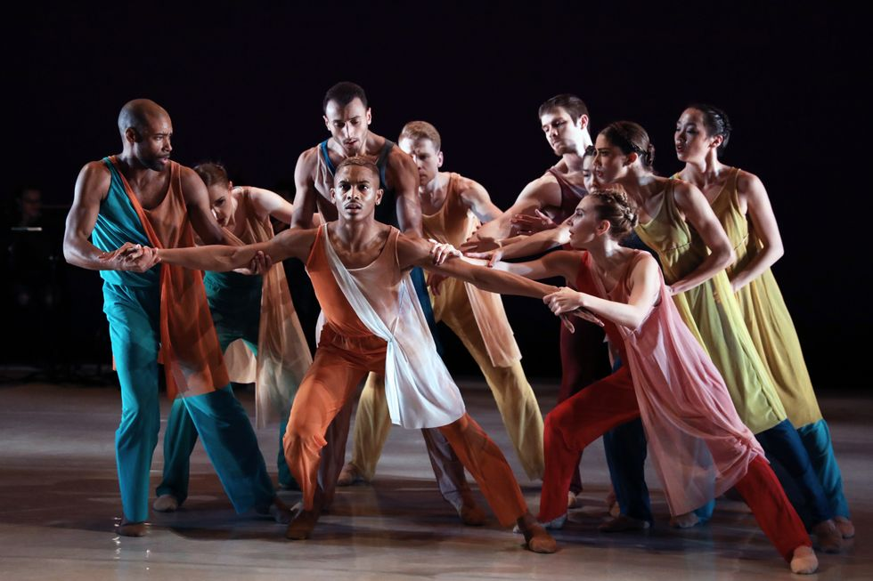 A group of dancers in brightly colored pants and tunics hold back Roderick Phifer, who stands in a parallel lunch with his arms spread in both directions.