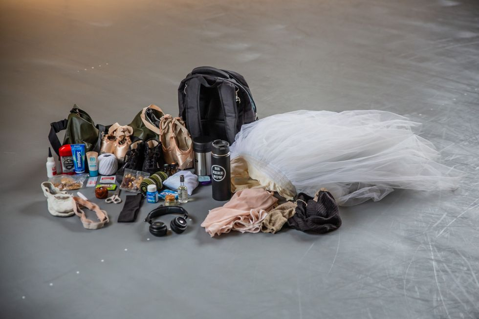 The contents of Lauren Lovette's emptied backpack and duffle back are laid out on the floor of a dance studio.