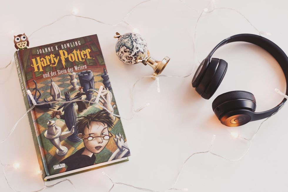 """""""Harry Potter"""" book aesthetically placed with headphones and lights"""