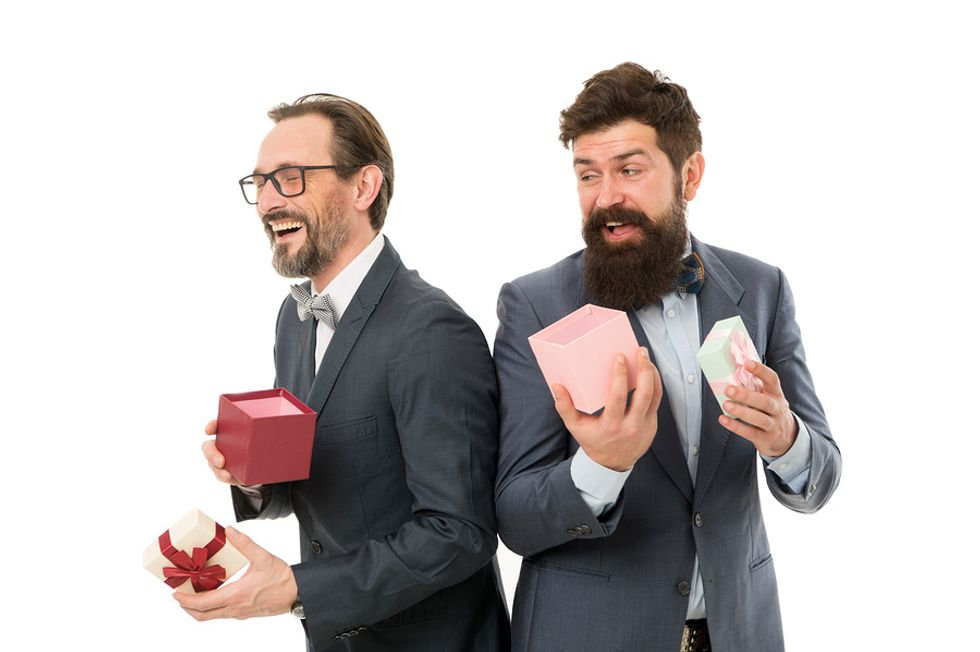 Two co-workers exchange gifts during an office holiday party.