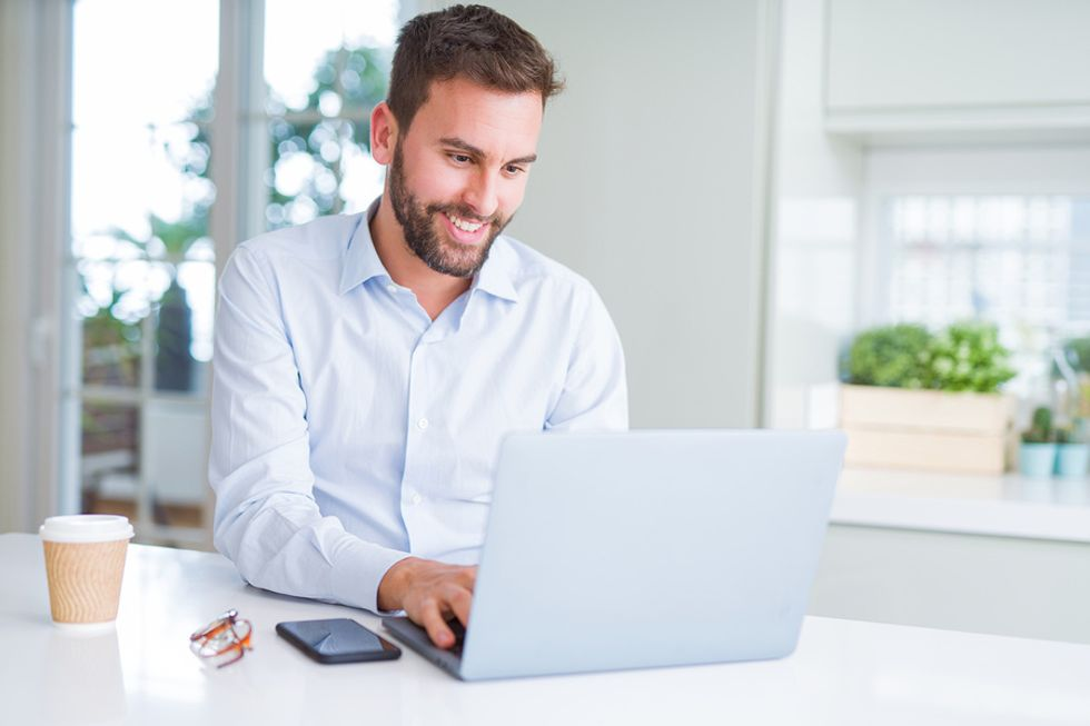 Young unemployed man establishing an online presence by writing a blog while he's looking for work.