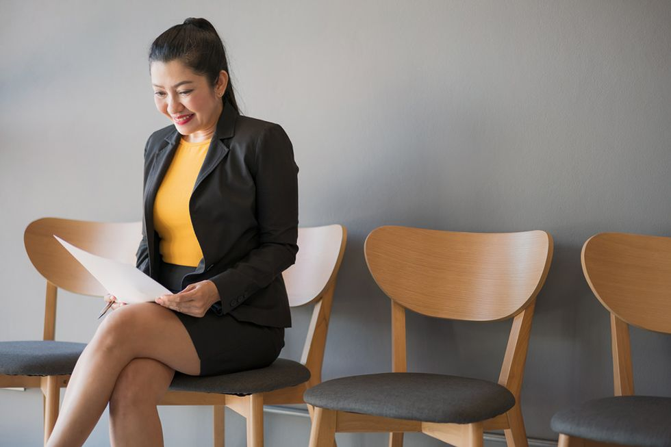 Teacher waiting for her interview while reading over her resume