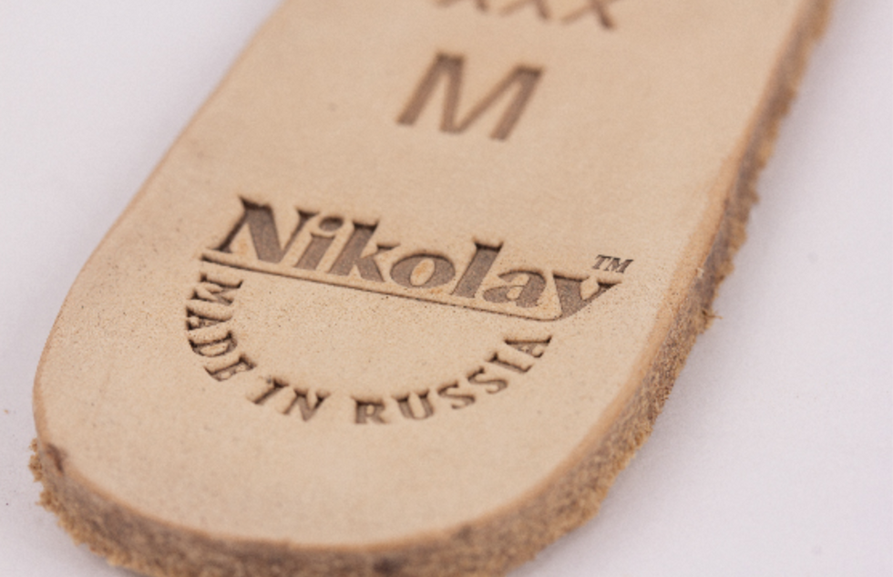 "A close up of the bottom of the sole of a pointe shoe, with the size and the words ""Nikolay: Made in Russia."""