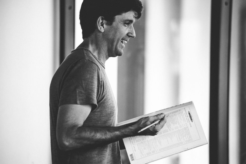 In black and white in profile, Lincoln Jones, wearing a t-shirt, holds a musical score and pencil. He is smiling.