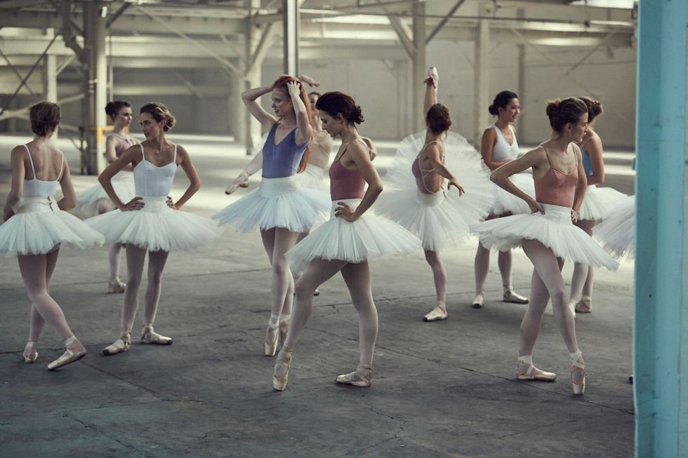 A number of ballerinas stand around a warehouse space wearing different colored leotards, white tutus, pink tights and pointe shoes.