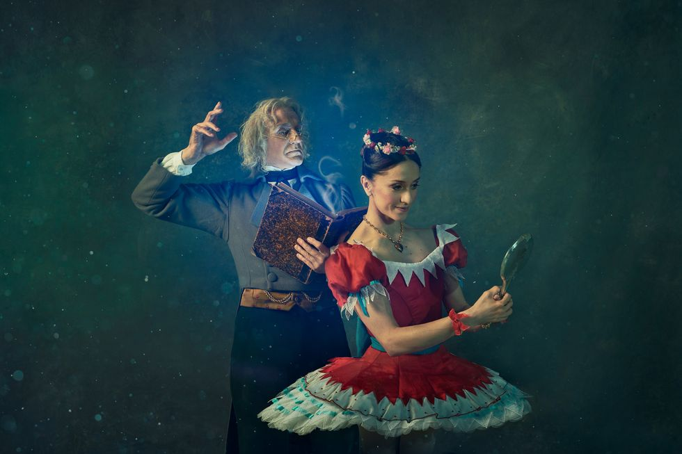 Marianela Nu\u00f1ez, as Swanilda, looks at her reflection in a handheld mirror, She wears a red tutu. Behind her, Gary Avis, as Dr. Coppelius, reads a book. He wears a gray jacket and white-haired wig.