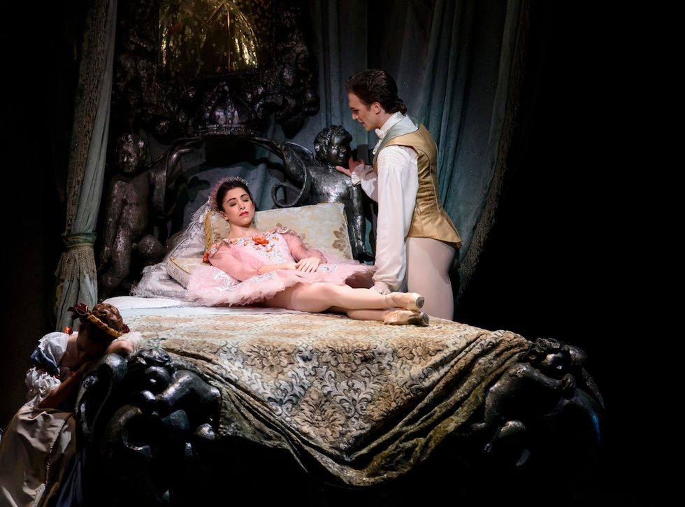 Yasmine Nagdhi, in a pink Sleeping Beauty tutu, lies on a bed while Matthew Ball, in a taupe silk jacket and tights, stands over her.