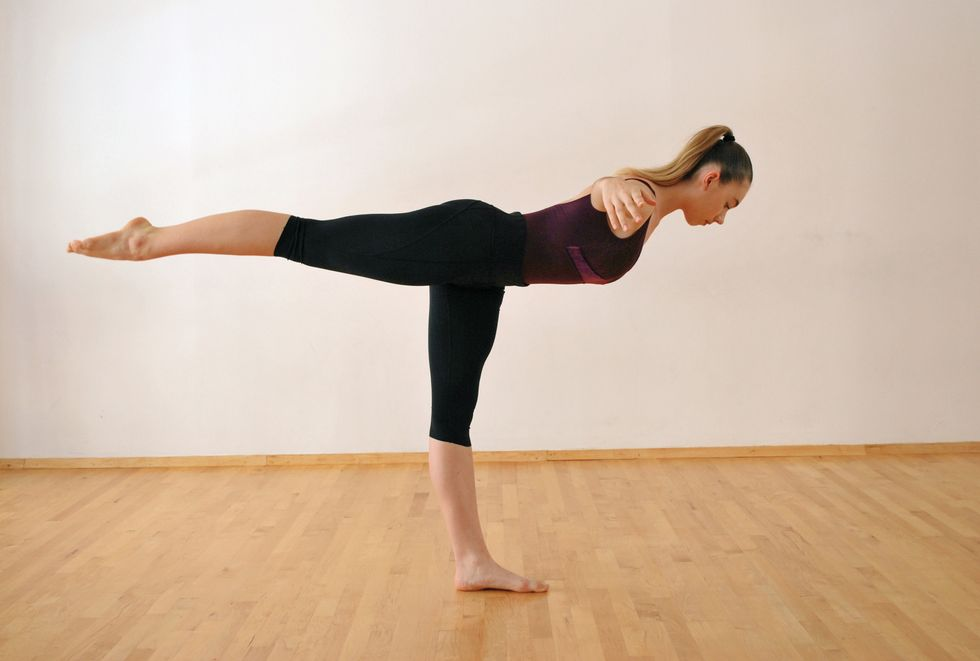 A dancer in a purple leotard and black leggings is in a white-walled studio with a wooden floor. She stands on one leg with the other leg extended behind her. Her body is parallel to the floor, and her arms are spread to the side.