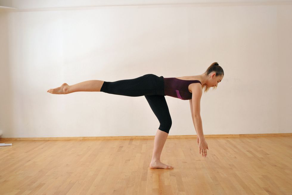 A dancer in a purple leotard and black leggings is in a white-walled studio with a wooden floor. She stands on one leg, which is bent. The other leg is extended behind her. Her body is parallel to the floor, and her arms reach toward the ground.