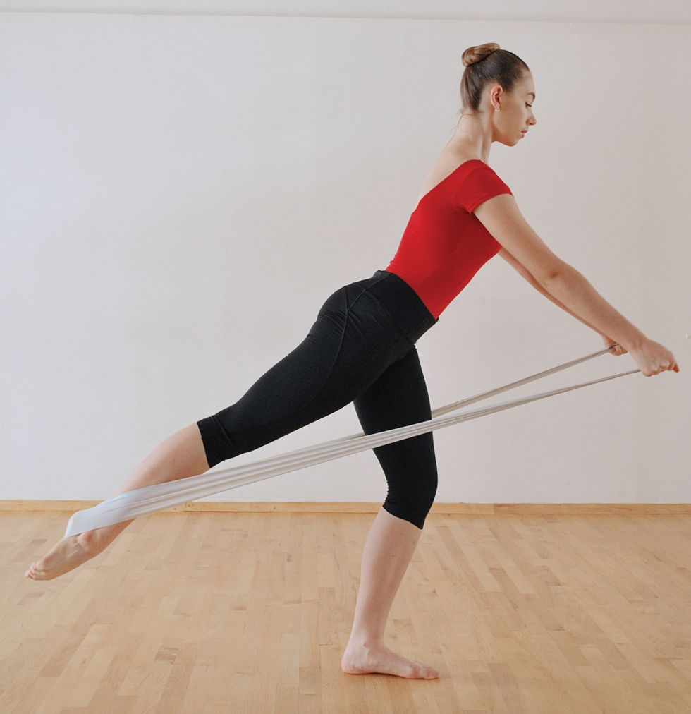 A dancer in black leggings and a red leotard stands with one leg extended behind her with an elastic band wrapped around it that she's holding with her hands.