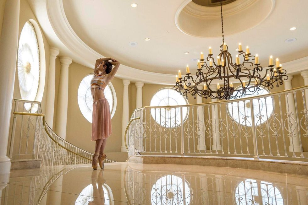 Isabell Mendez in a pink skirt, crop top and pointe shoes stands in an elaborate, fancy hall above a wrought iron staircase, with a large chandelier.