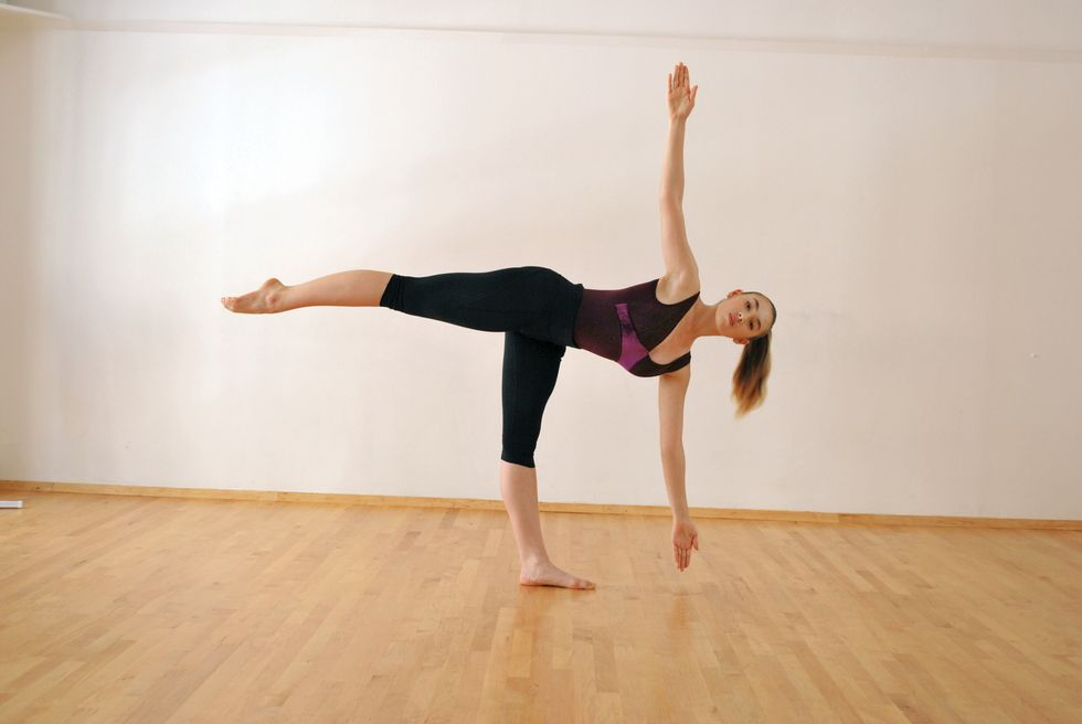 A dancer in a purple leotard and black leggings is in a white-walled studio with a wooden floor. She stands on one leg with the other leg extended behind her, and her body is rotated open so that her torso faces the camera. Her arms are extended vertically.