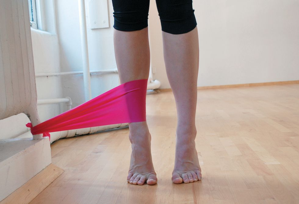 A dancer stands in black leggings on a wooden studio floor. We only see her legs. She is standing in relev\u00e9, and a pink elastic band attaches her ankle to the base of a white radiator.