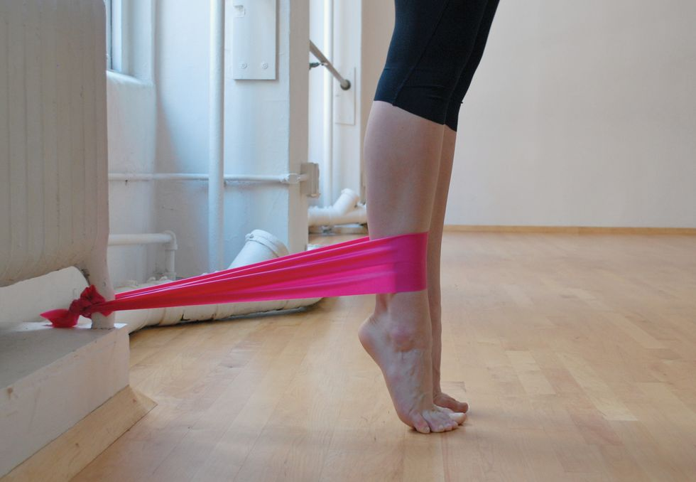 A dancer stands in black leggings on a wooden studio floor. We only see her legs. She is standing in relev\u00e9, and a pink elastic band attaches her ankle to the base of a white radiator. We see her legs in profile..