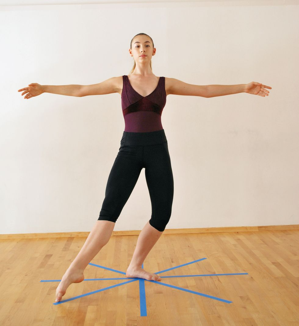 A dancer in a purple leotard and black leggings is in a white-walled studio with a wooden floor with a blue tape star on the floor. She stands in pli\u00e9 with one leg in tendu to the side. Her arms are in second position.