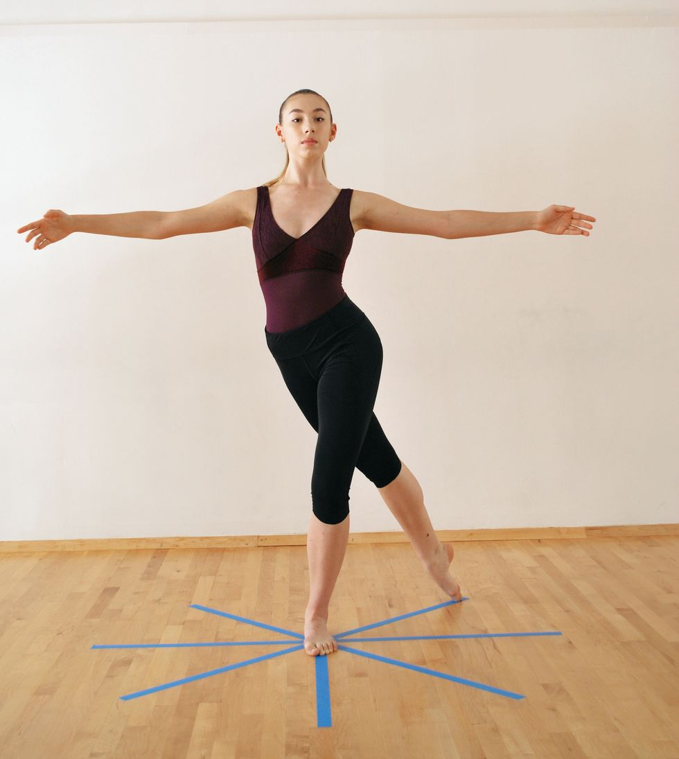 A dancer in a purple leotard and black leggings is in a white-walled studio with a wooden floor with a blue tape star on the floor. She stands with one leg extended behind her on the floor. Her arms are in second position.