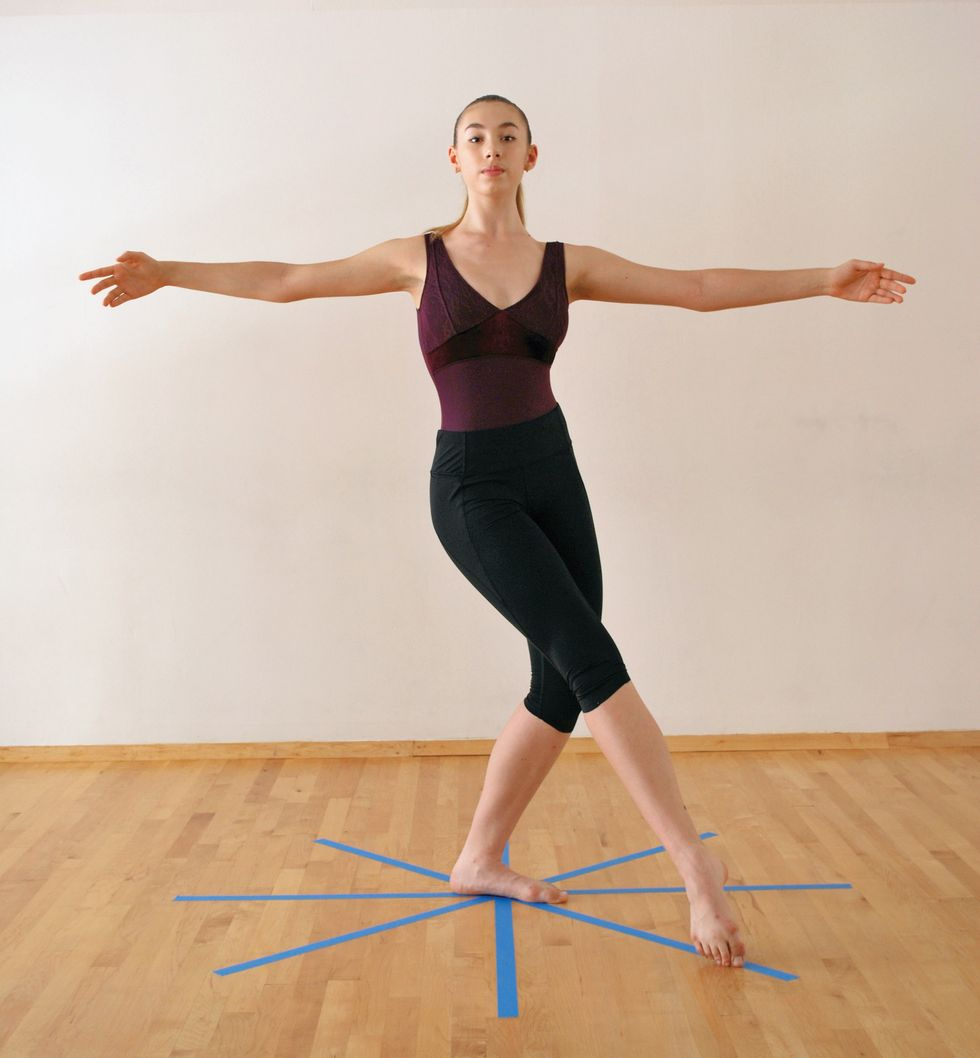 A dancer in a purple leotard and black leggings is in a white-walled studio with a wooden floor with a blue star taped on the floor. She stands in pli\u00e9 with one leg extended in tendu in front of her. Her arms are extended in second position.