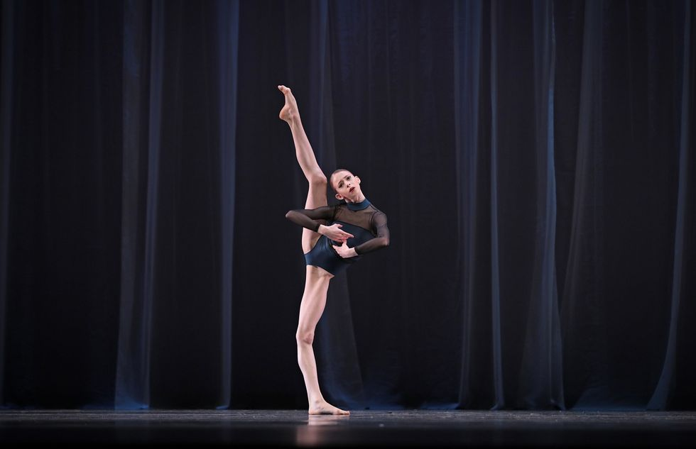 A dancer stands in a navy and black sheer leotard with one leg extended way above her head.