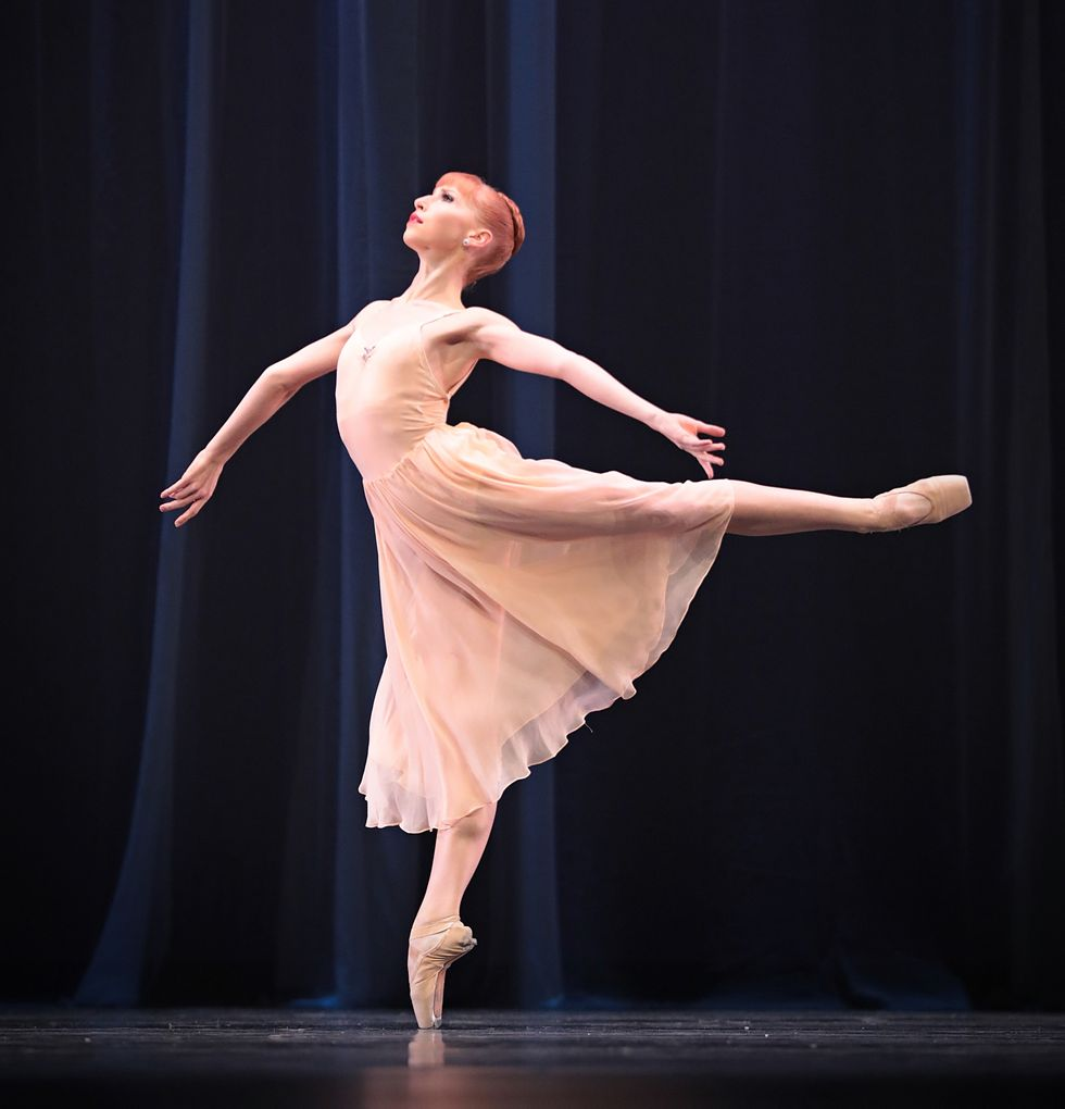 A dancer in a pink chiffon dress with red hair in a bun stands in a 90-degree arabesque, with her arms stretched out.