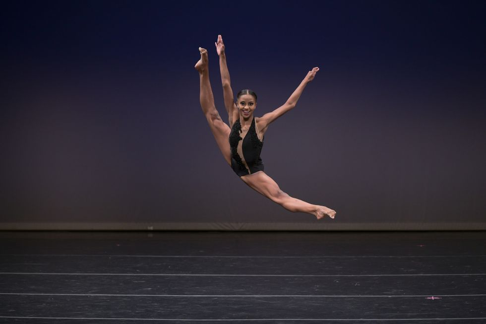 Madison Brown, in a black leotard costume, leaps in the air with her legs over extended.