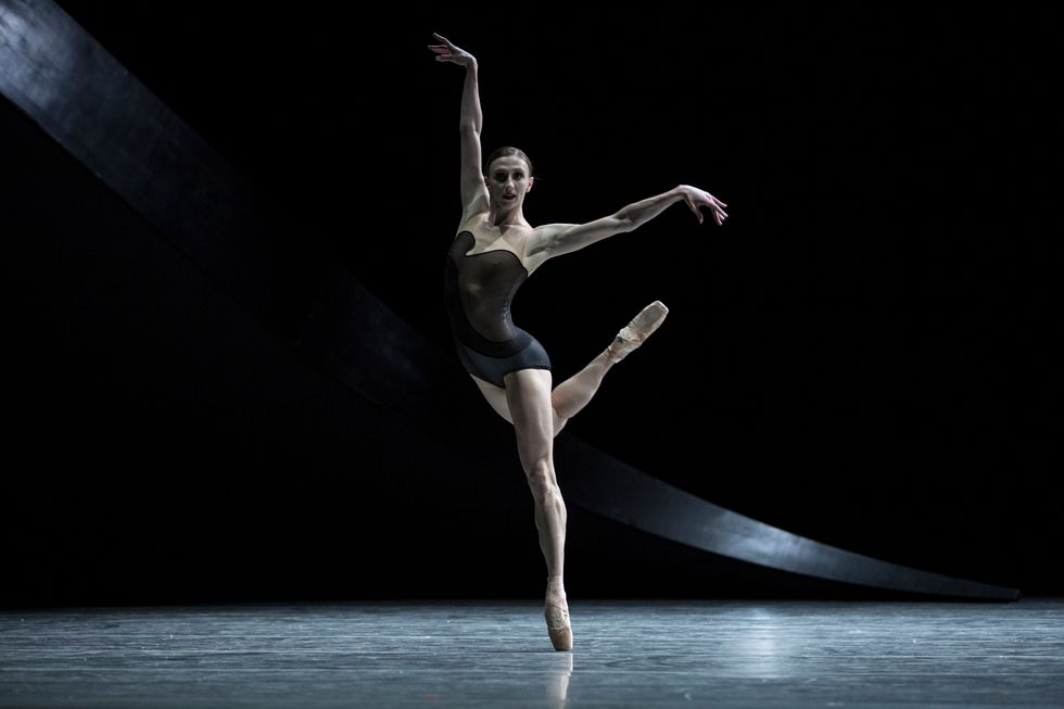Macy onstage in a dark background wearing a black leotard costume and pointe shoes. One leg is extended in a kind of attitude behind her.