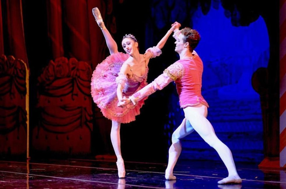 Sam Ainely, in a pink tunic and white tights, partners a ballerina in a purple tutu on pointe.