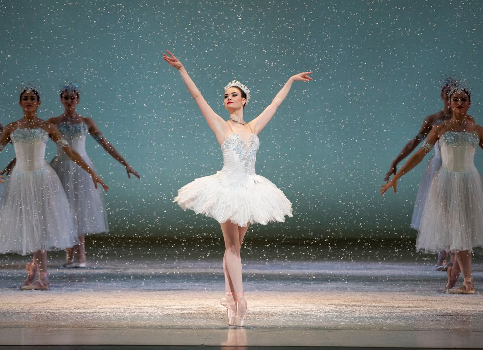 Elizabeth stands onstage with her feet together in sus-sous on pointe. She wears a white tutu and crown, and there is fake snow falling around her.