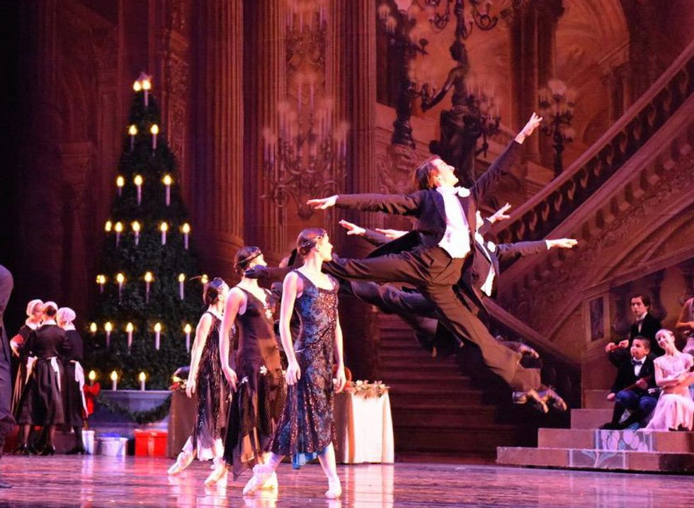 Chandler Proctor, in a black tuxedo costume, splits his legs into sissonne during the Nutcracker's party scene. He is surrounded by other dancers in black dresses and tuxedos.