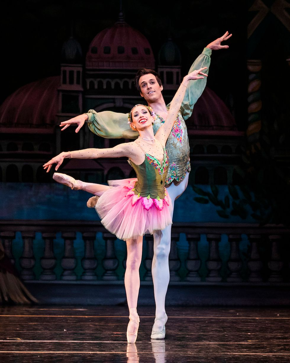 Katherine Lawrence, in a green and pink tutu, and Chase O'Connell, in white tights and a green tunic, balance on their right leg with their left leg lifted behind them in attitude.