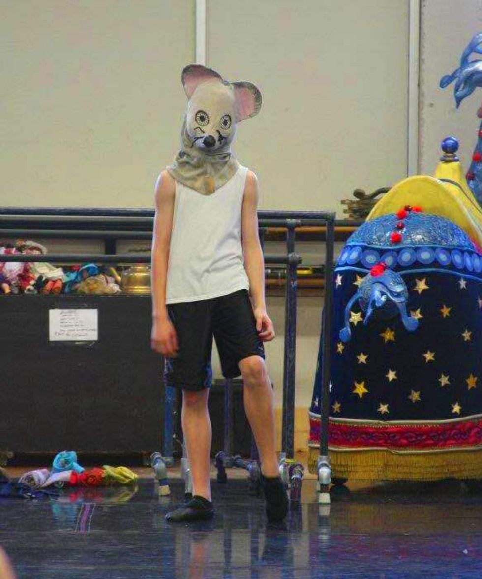 Sam Ainley, in a mouse headpiece, white sleeveless T-shirt, black shorts and black ballet shoes, listens to rehearsal notes in a cluttered dance studio.