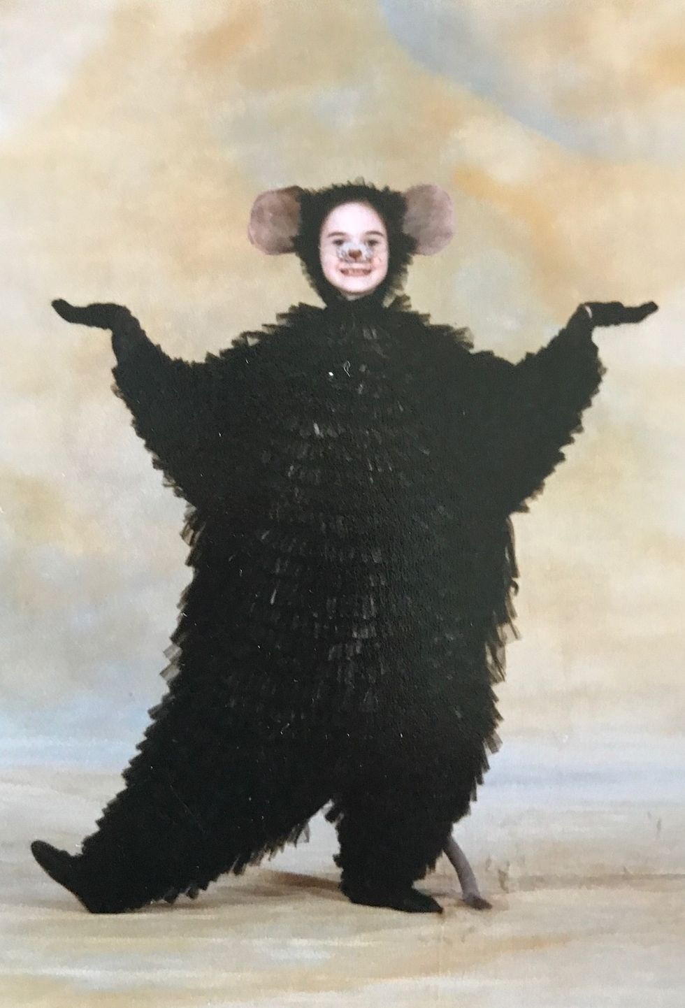 Elizabeth Powell, as a child, poses in a fluffy black mouse costume and headpiece. She wears makeup of a mouse nose and whiskers on her face.