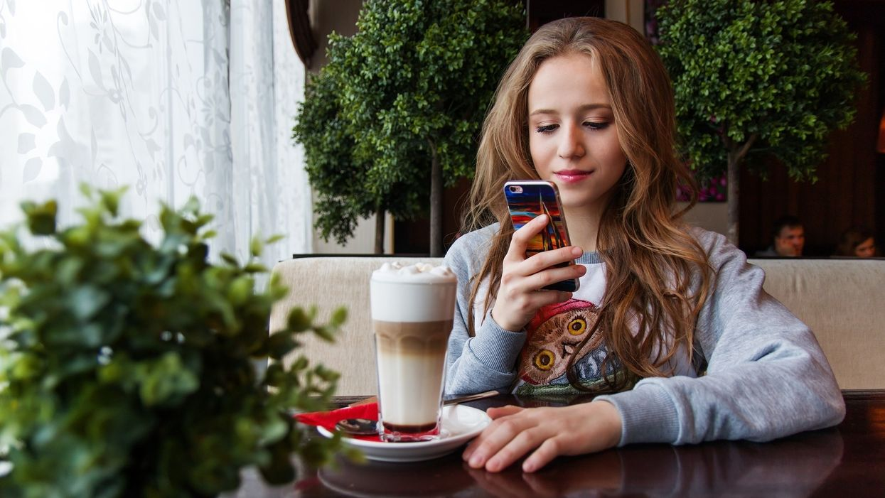 Teenage girl using her phone in a restaurant