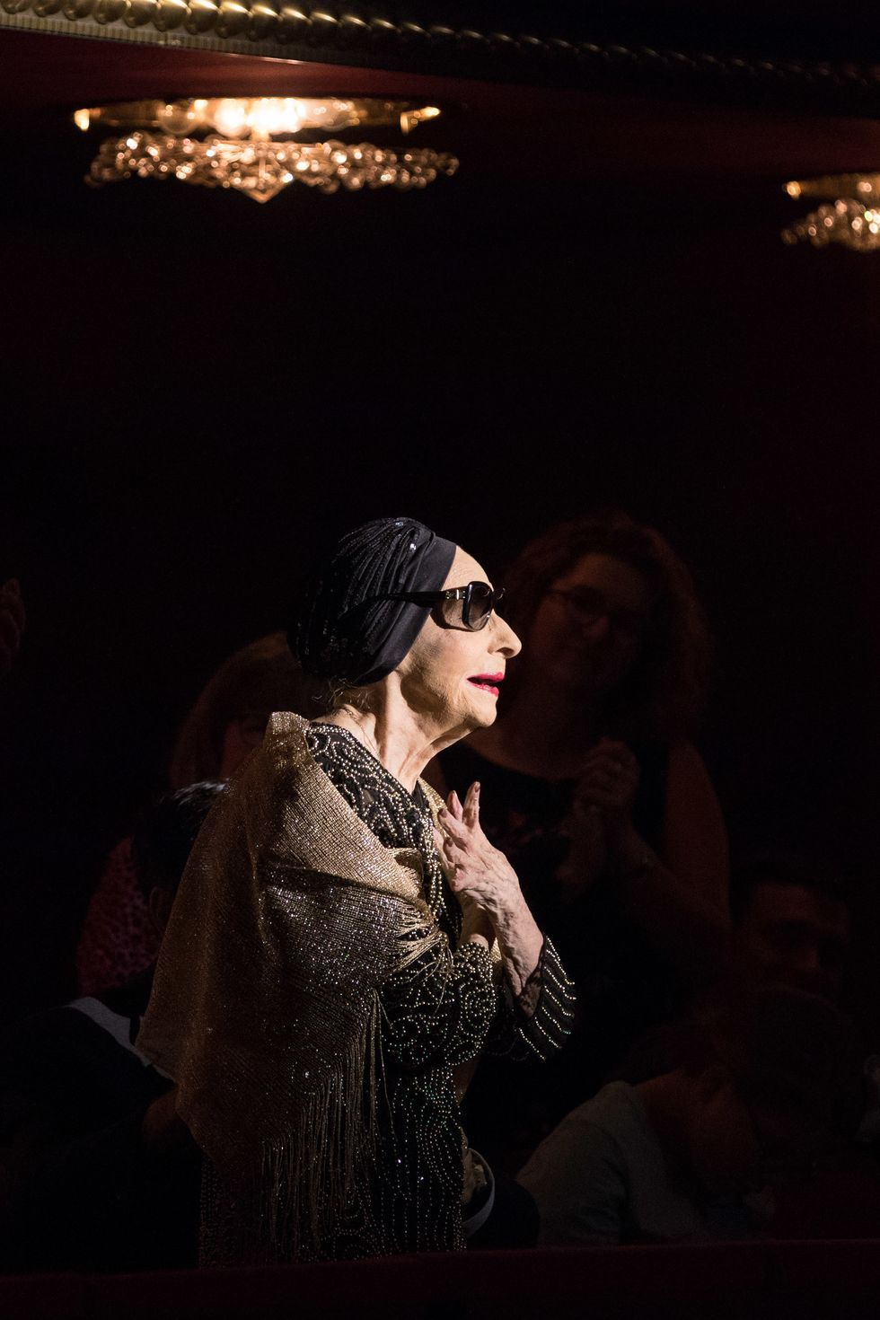 An elderly woman wearing sunglasses and a black headscarf stands in a spotlight, taking a bow.