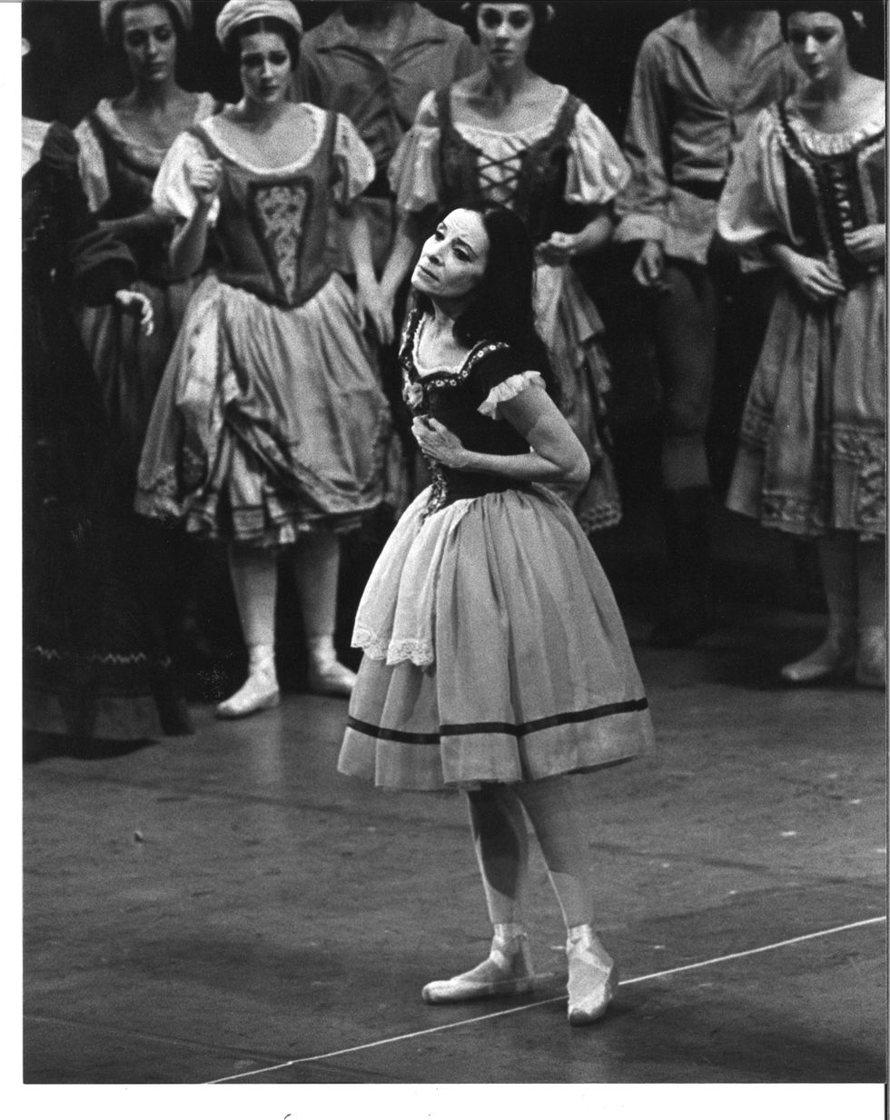 In this black and white photo, a dark haired ballerina in a peasant costume clutches her heart onstage.