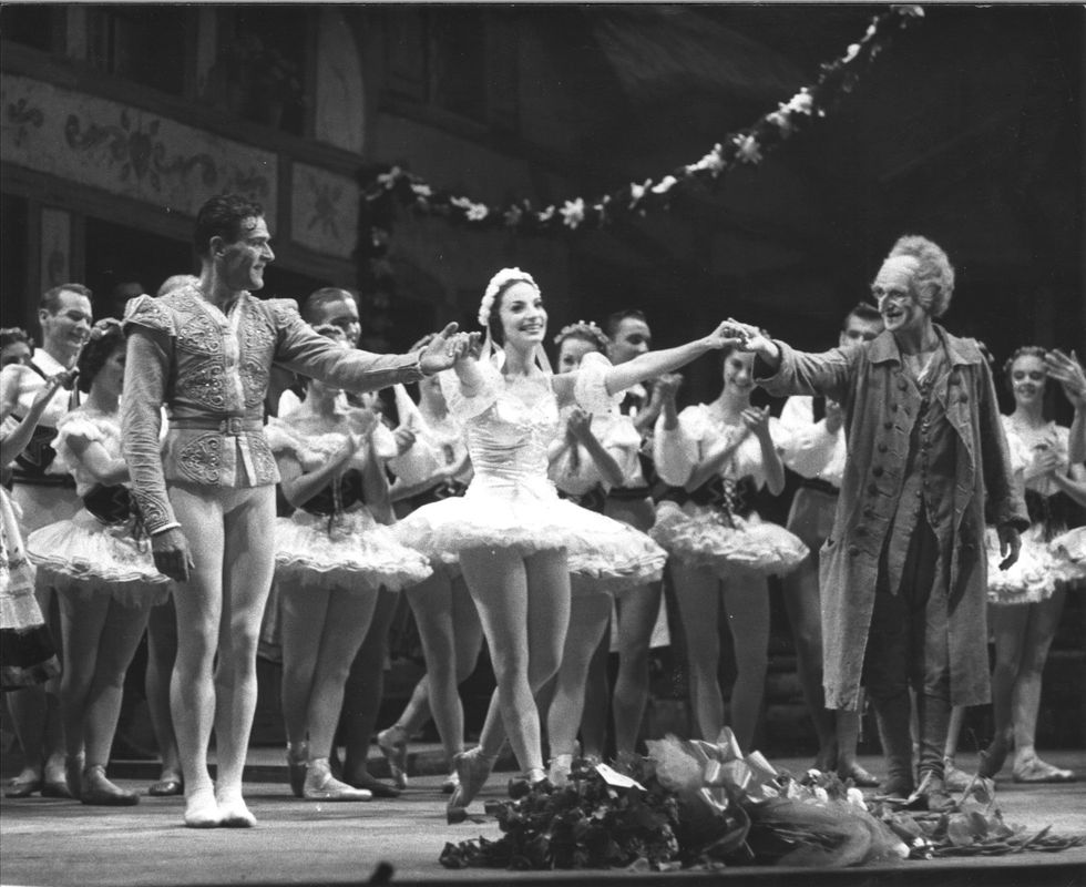 I this black and white photo, a ballerina in a white tutu takes a bow on a crowded stage.