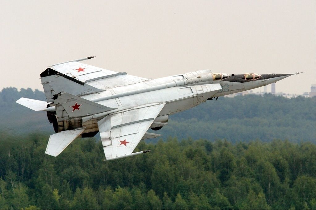 A two-seat trainer version of the MiG-25 flies over forested land.